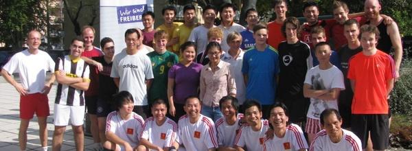 Buntes, breitformatiges Gruppenbild mit internationalen Personen in Sportkleidung
