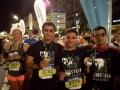 Läufer mit Medaillen bei einem Nachtlauf im Trubel einer Stadt